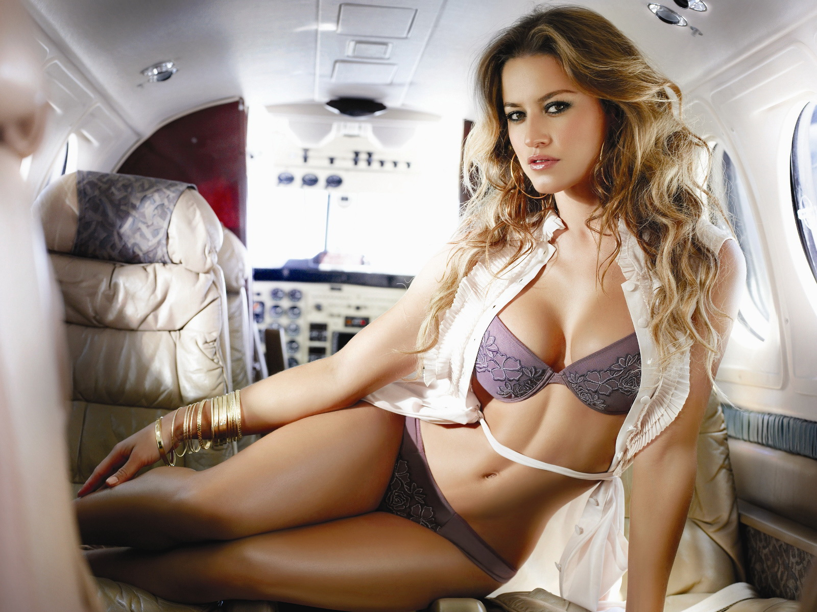 Curly-blonde-girl-in-lingerie-in-a-private-jet-plane-with-white-vest-wallpaper_2698